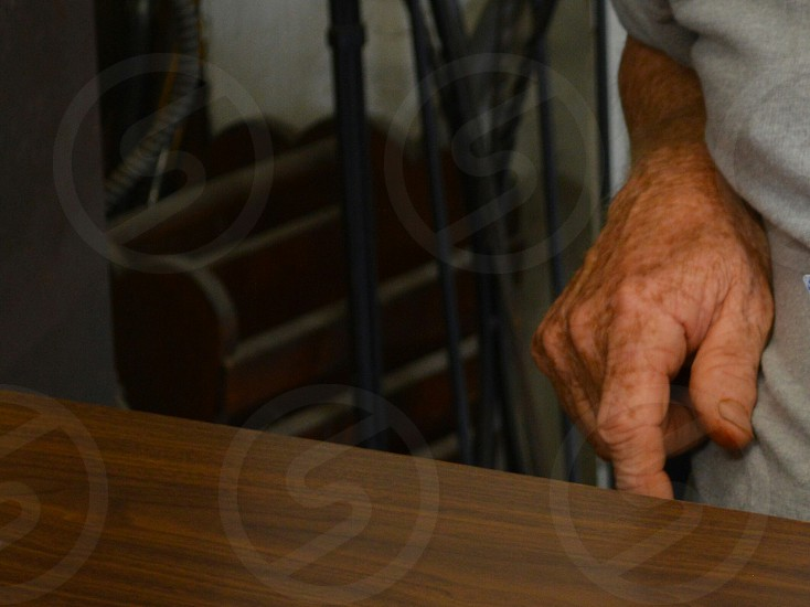person's hand near wood table photo
