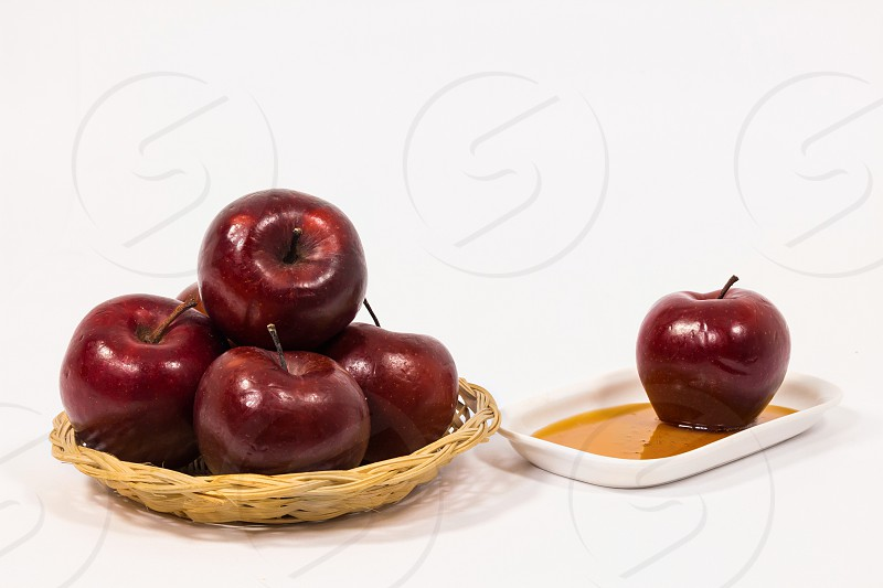 Pile of red apples and red apple on white plate with honey isolated on a white background. Symbols of Jewish New Year - Rosh Hashanah.  photo