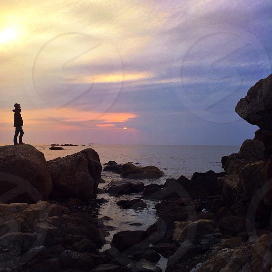 man on rock standing with sunset view photo