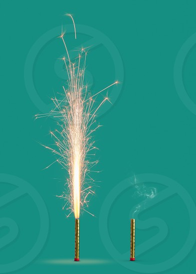 Burning firework with bright sparkes and smoke from burnt candle on a turquoise background copy space. Concept of festive event. photo