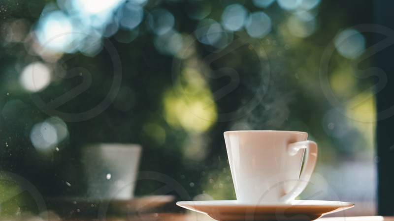 Coffee cup on the wooden table and green bokeh background in the morning sunrise. photo