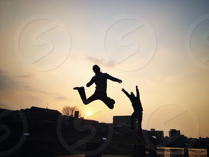 man and woman jumping silhouette portrait  photo