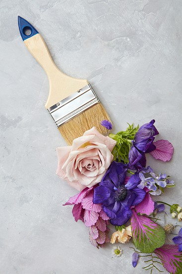 Purple and pink flowers and paint brush on stone background. Flat lay. photo