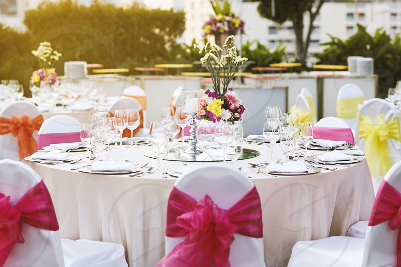 Warm sunset light with luxury wedding reception dinner table setting with empty glasses of water wine and dinnerware with flower decoration and white fabric cover chairs with pink sash photo