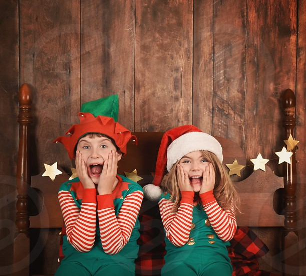 Two funny young children are surprised and excited sitting on a bed with Christmas pajamas with a wood wall. Use it for a holiday message idea. photo