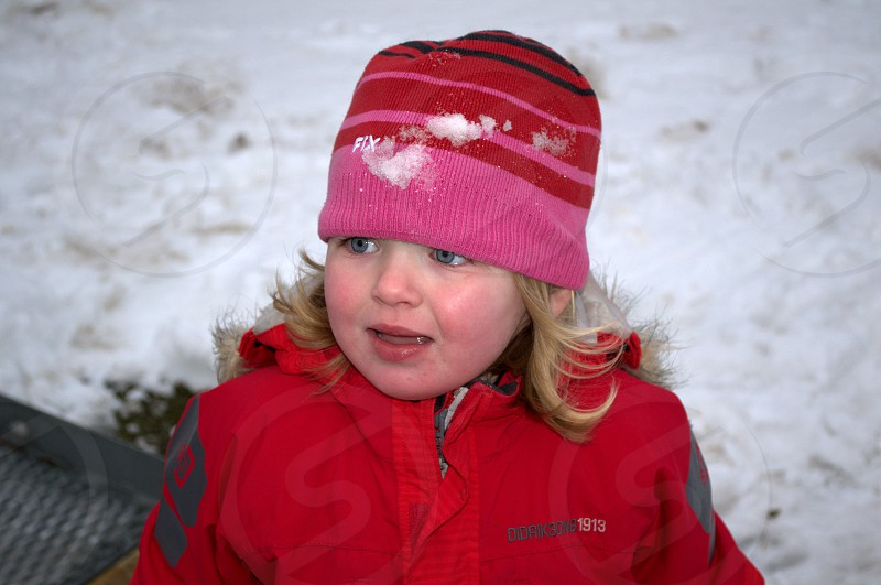 girl in blonde hair in snow with blue eyes and red coat and pink and red striped cap photo