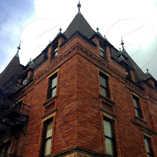 brown brick building with roof spires photo