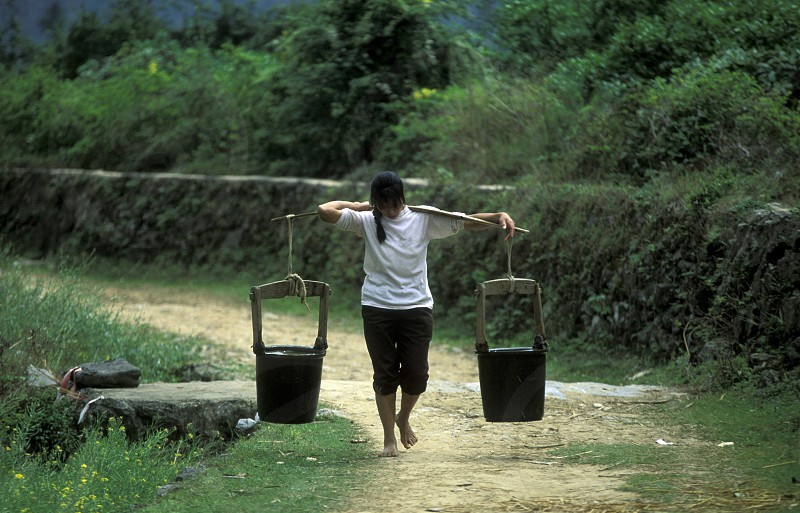 a women with water at the farmland near the town of Yangshou near the city of  Guilin in the Province of Guangxi in china in east asia.  photo