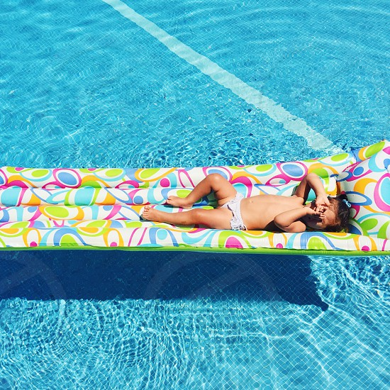 close up photo of toddler lying on green white and blue floater on swimming pool photo