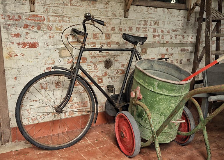 Old bicycle against a whitewashed brick wall in an outbuilding photo