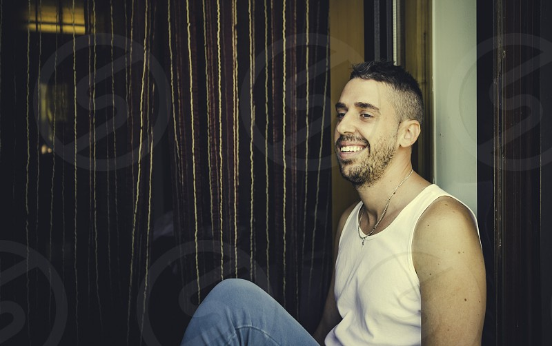 Young man with a beard smiling sitting in the window box photo