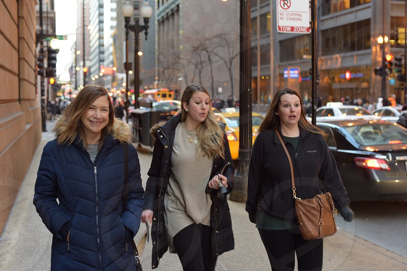 Walking girls friends city winter cold Chicago loop urban female real people traffic downtown shopping coworkers family women candid  outdoor talking smiling happy busy professionals moving natural light afternoon daylight  photo