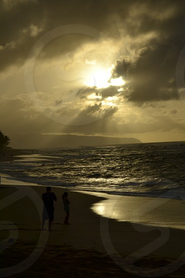 Sunset at North Shore Hawaii.  The beach was really nice the sound of the ocean wave It would be a good place for people to unwind think and reflect on life. photo