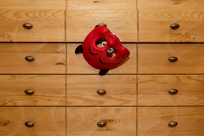 The carnival mask hangs on the chest of drawers. photo
