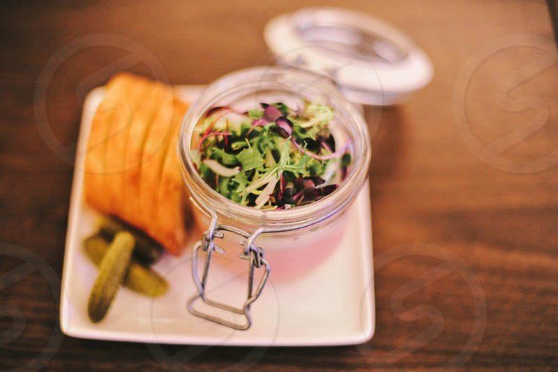greens salad in a mason jar with bread and pickles on a white plate photo