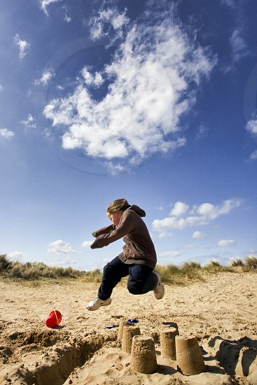 Young boy jumping over sand castles on a sunny day photo