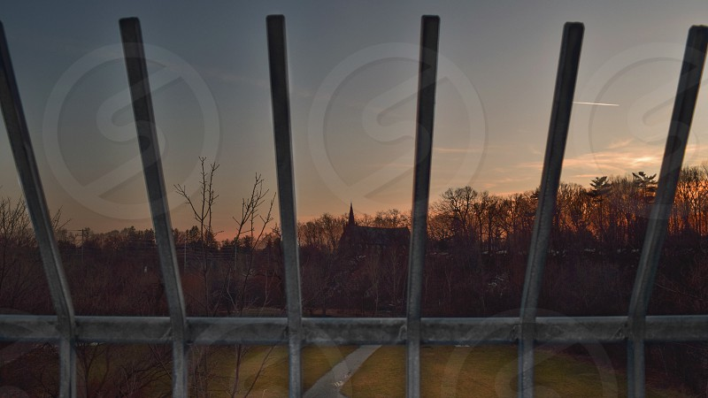 a sunset shot behind a fence looking out towards a park area and a church in the background in front of a sunset photo