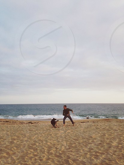 man running on shore with black and beige dog photo