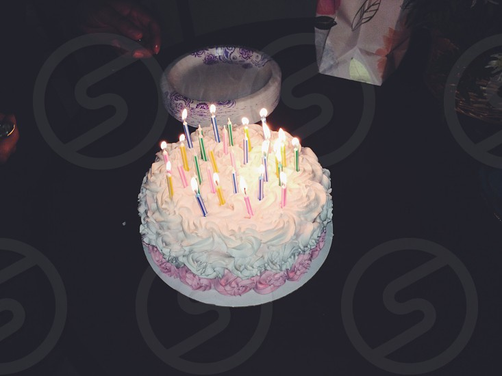 birthday cake with assorted-color candles on top of black table photo