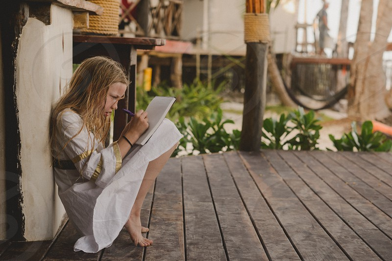 Girl writing letter at the beach photo