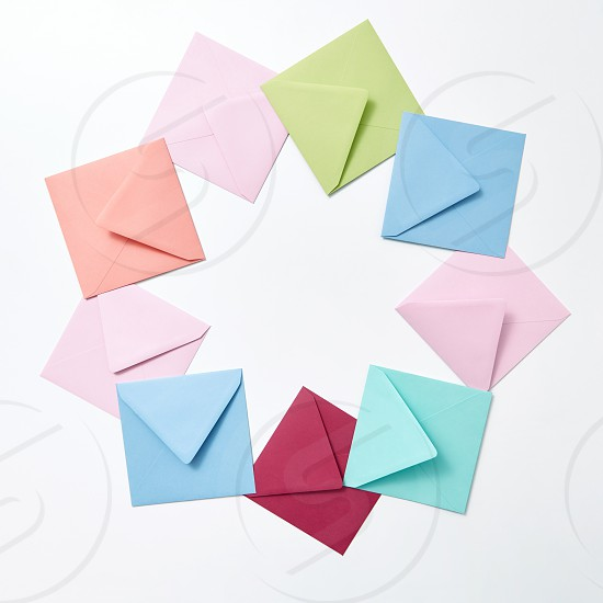 Empty colorful hndcraft envelopes in the shape of round frame on a light gray background with copy space. photo