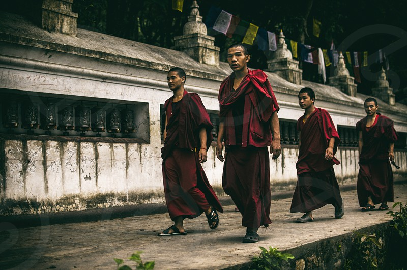 4 monks in red 3/4 sleeved top walking on the gray concrete pavement photo