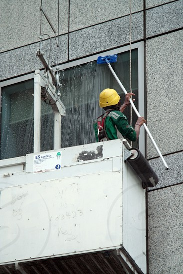 man in green shirt cleaning window on building photo