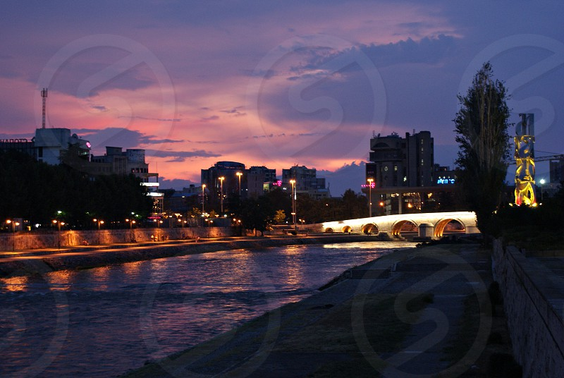 orange streetlights turned on by the river near white bridge with a background view of city photo