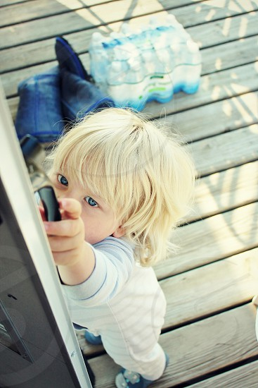 child with blond short hair touching black handle during daytime photo