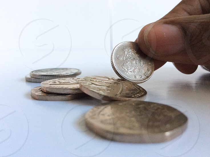 A hand counts some loose change on a white background photo