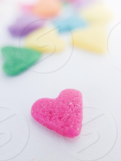 tiny small little pink blue green yellow purple multicolor heart love valentine sweet candy close up sugar photo