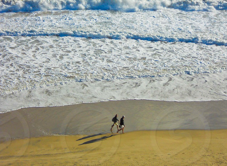 two people walking at the shore near crashing seawater waves during daytime photo