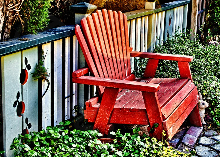 Red Adirondack chair sits on a garden path near a fence. photo