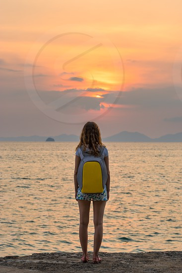 One young woman traveller with a backpack stands and looks on the sea at the beautiful sunset and seascape. Full rear view. photo