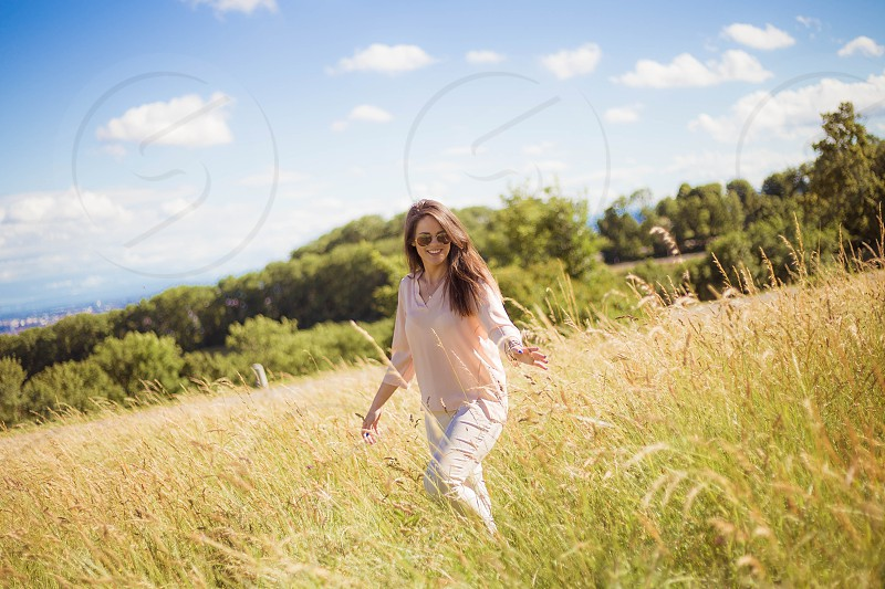 woman in white long sleeve shirt and pants waking in brown and green grass field during daytime photo