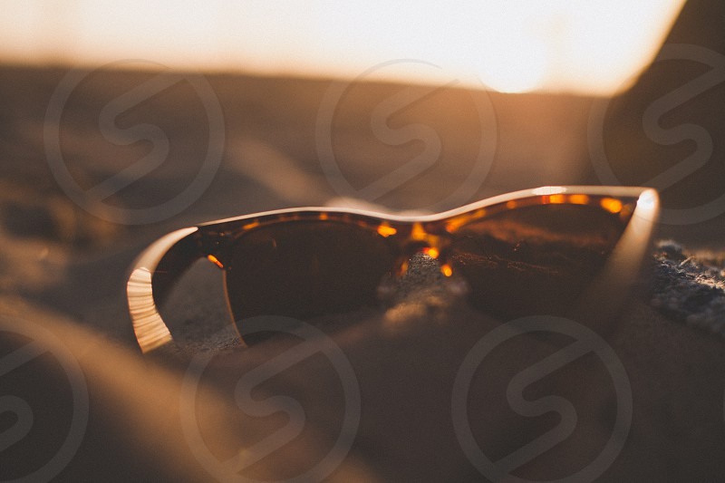 brown sunglasses on brown sand photo
