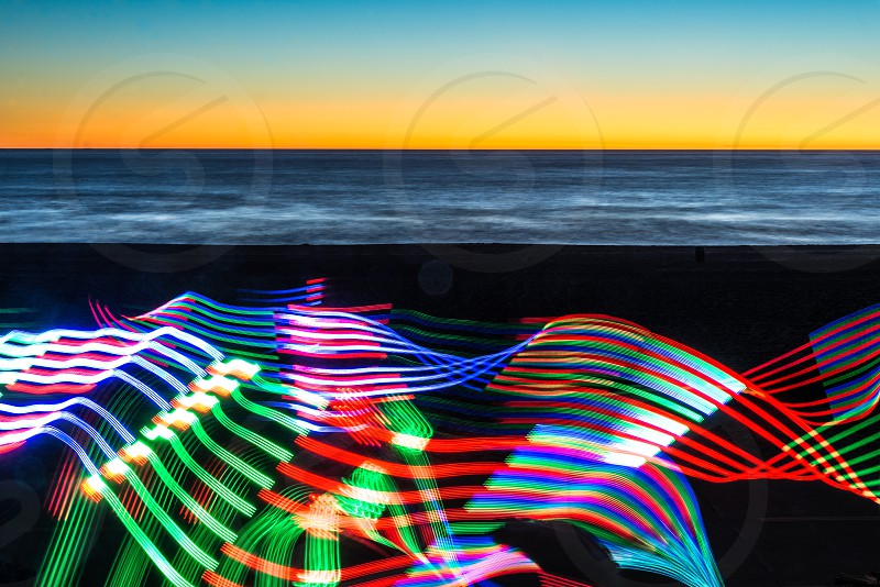 mutlicolored led lights at beach with calm water under blue and yellow skies photo