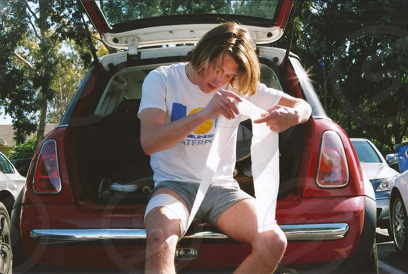 man in white shirt sitting at the back of the car photo