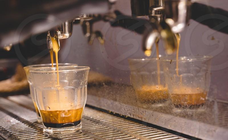 espresso coffee shot pouring into piccolo clear grass from a espresso machine in cafe. close-up photo