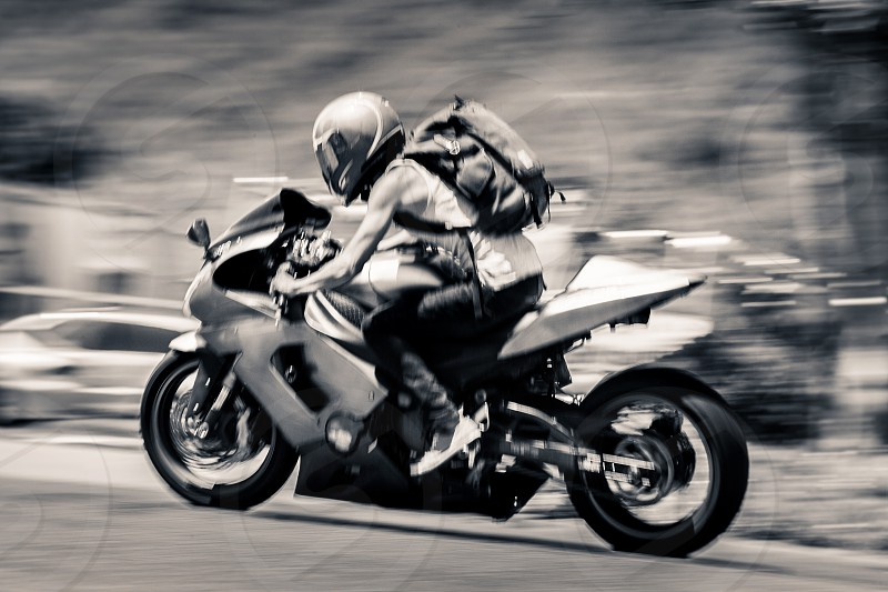 A motorcyclist wearing a helmet and backpack races down the road on his street bike. photo