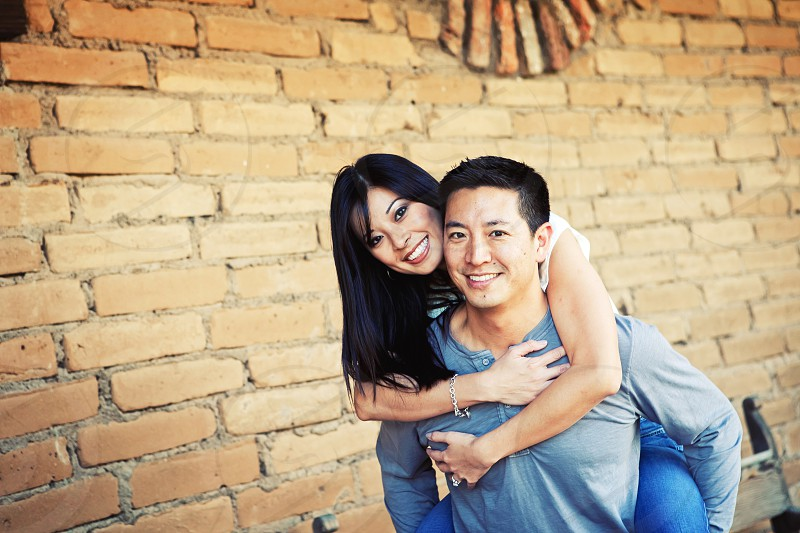 man in blue long sleeved shirt carrying woman and both smiling photo