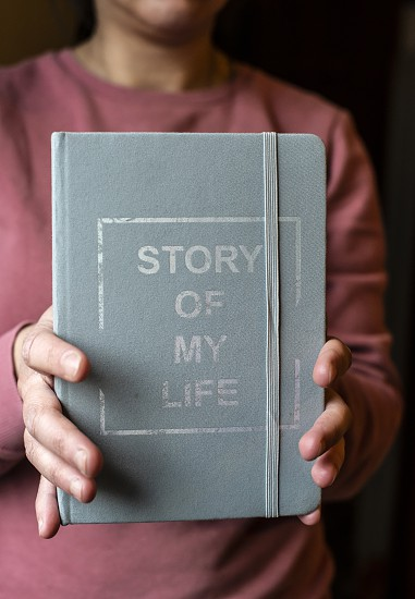 Woman hold notebook. Book notes for the Story of my life. Personal memoirs notes concept. Hands hold book. photo