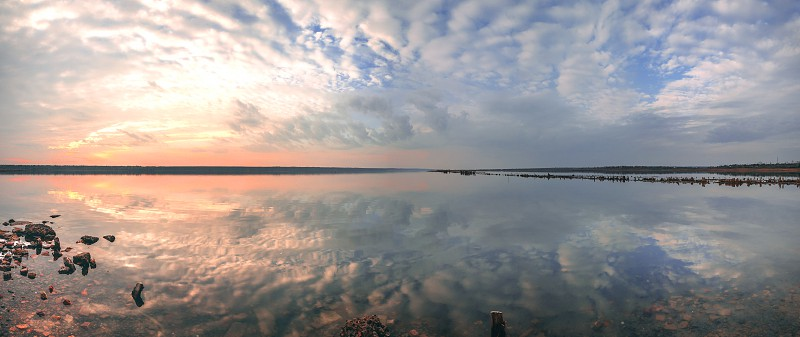 Sunset clouds reflected on the water surface on a warm summer evening photo