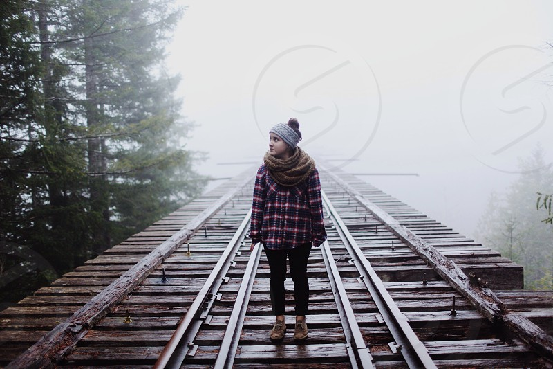 woman standing on brown wooden bridge photo