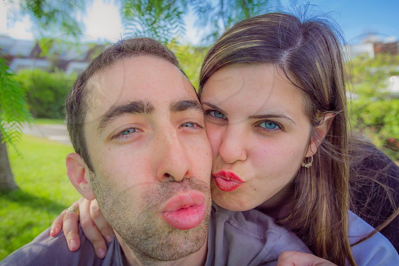 Couple having fun making duckface and taking selfie picture in the park. photo