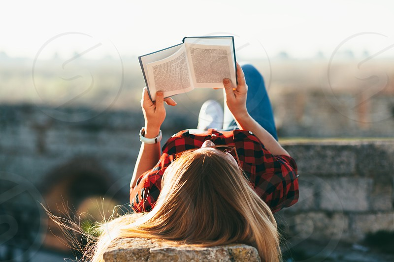 Young woman enjoying reading a book in public park photo