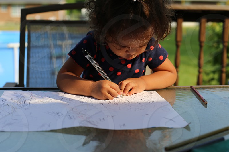 Toddler writing a note to her momma photo