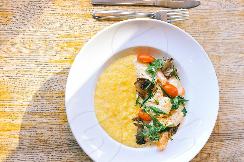 grape tomatoes and chicken with corn chowder in a white bowl on a wood tble photo