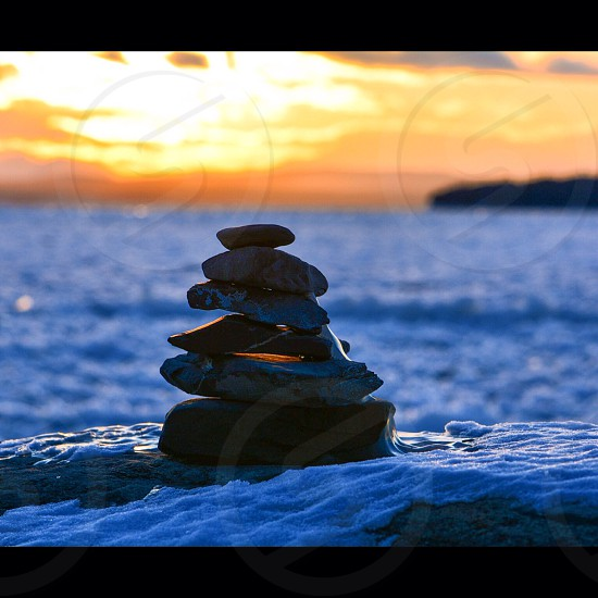 reflective and meditative rock cairn on waterfront at sunset photo