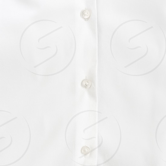 Close-cropped shot of white buttons on a white shirt. photo